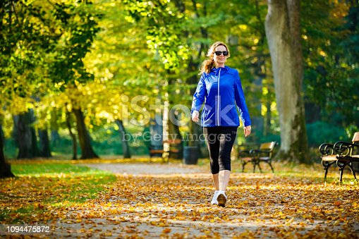 Mid aged woman running in city park