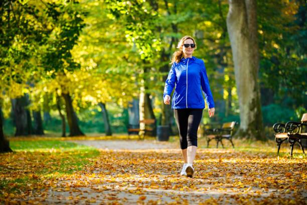 kobieta w średnim wieku biegająca w parku miejskim - wędrować zdjęcia i obrazy z banku zdjęć