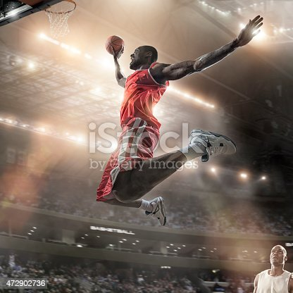 istock Mid Air Basketball Slam Dunk Jump 472902736