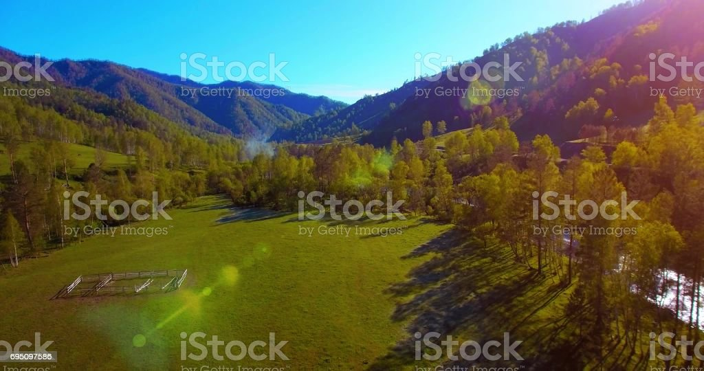 Mid air flight over fresh mountain river and meadow at sunny summer morning. Rural dirt road below stock photo