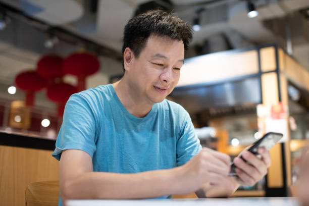 Mid Asian adult surfing net with smart phone at cafeteria Mid Asian adult using smart phone while waiting for food to be served at cafeteria. 5G & Wireless Technology, Family Bonding & Togetherness Concepts. handsome middle-aged asian guy stock pictures, royalty-free photos & images