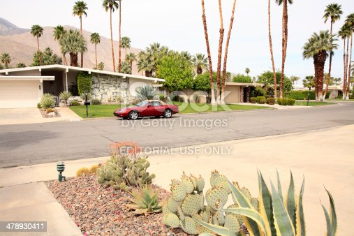 Palm Springs,United States- March 11,2014: Mid Century home with arid desert plants,palms and luxury red Jaguar parked in front of home.