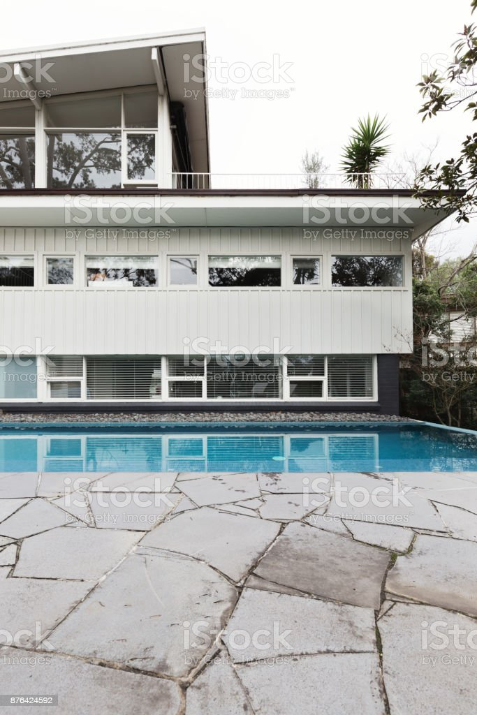 Mid century home exterior with blue tiled swimming pool and crazy paving patio stock photo