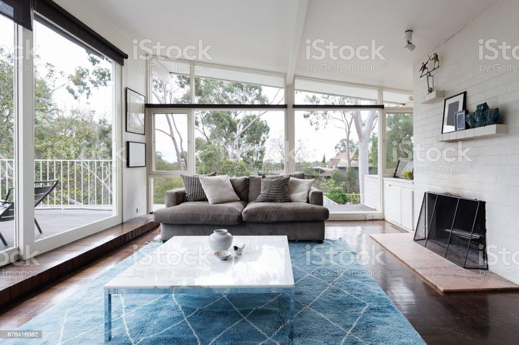 Elegant Mitte Des Jahrhunderts Moderne Wohnzimmer Mit Großen Fenstern An Den  Australischen Baumkronen Lizenzfreies Stock Foto