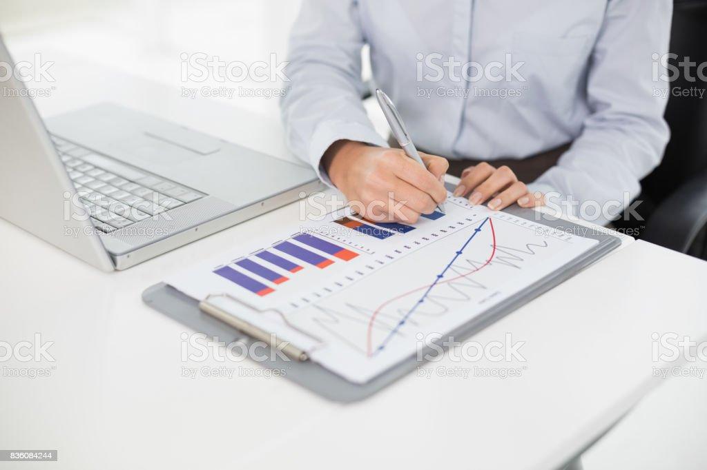 Seção intermediária de uma empresária com gráficos e portátil - foto de acervo