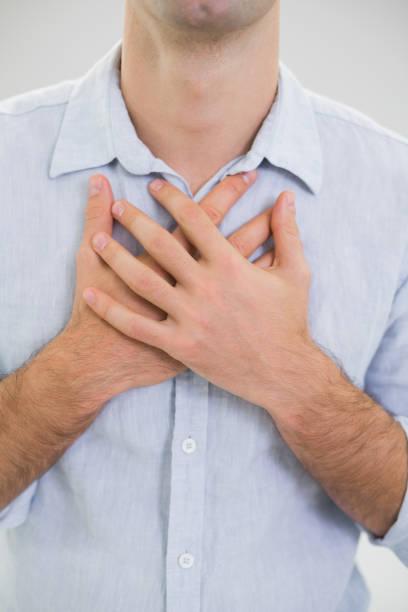 mid section of a man with chest pain - mão no peito imagens e fotografias de stock