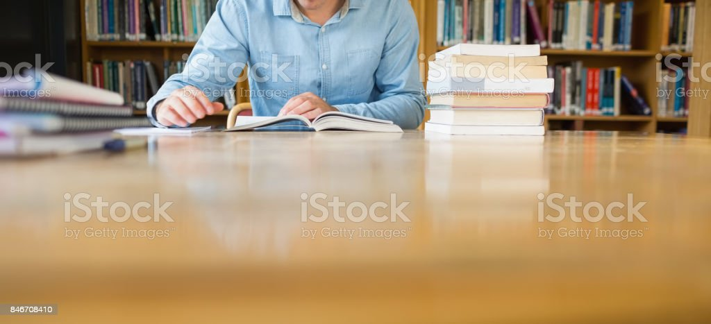 Mid section of a student studying at library desk stock photo