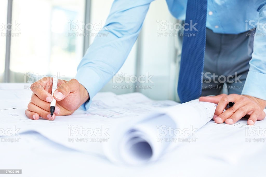 Mid section of a young architect working on blueprints stock photo