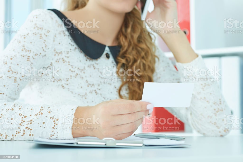 Mid section of a young woman talking on the mobile phone holding bisness card in hand. stock photo