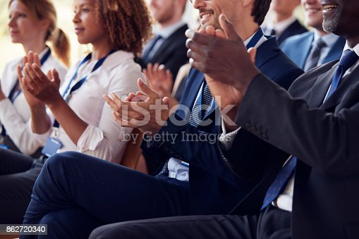 istock Mid section of applauding audience at business seminar 862720340