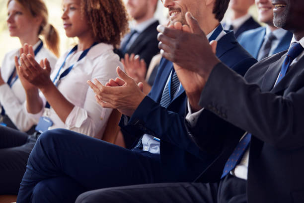 Mid section of applauding audience at business seminar stock photo