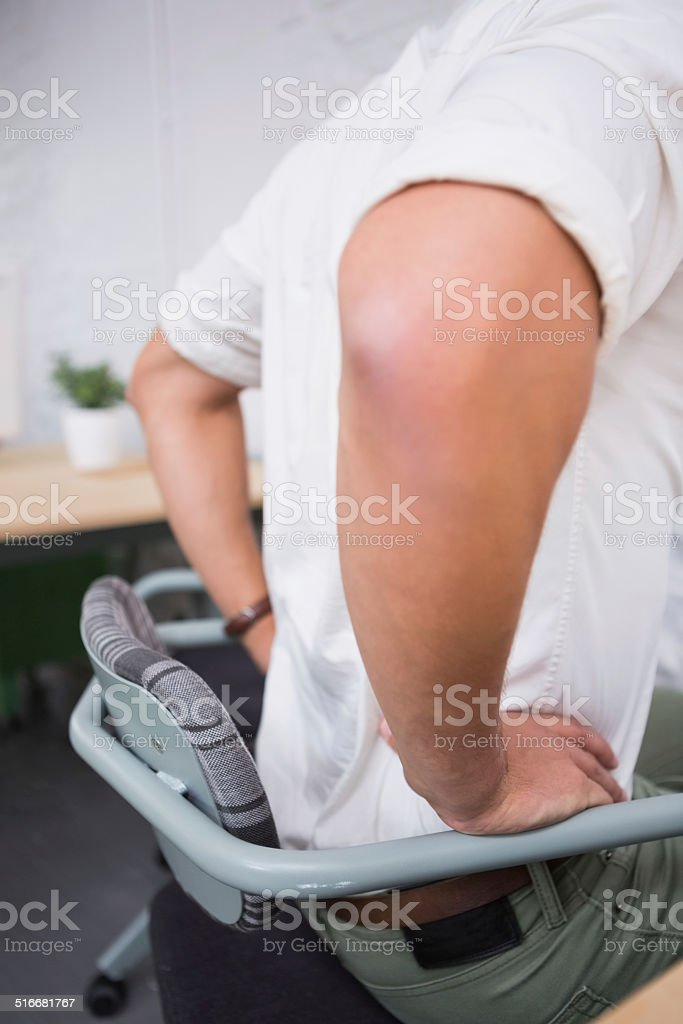 Mid section of businessman suffering from backache stock photo