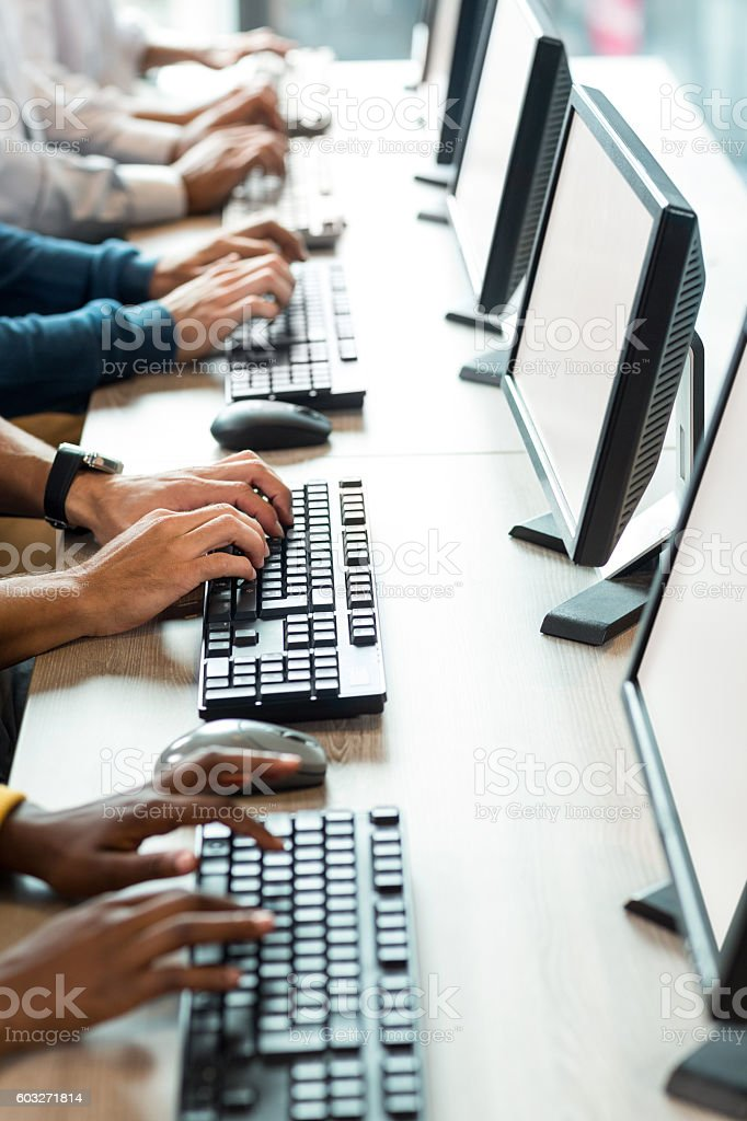 Mid section of colleagues working on computer stock photo