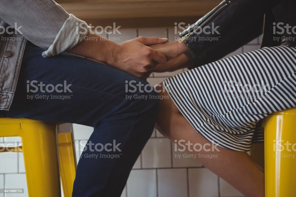Mid section of couple holding hands on stool in cafe stock photo