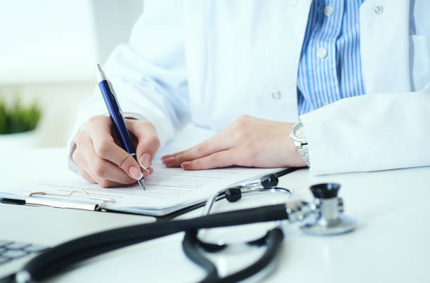 Mittlere Rand der Ärztin schreibt Rezept an die Patientin am Arbeitstisch. Allheilmittel und Lebensrettung, verschreibende Behandlung. – Foto