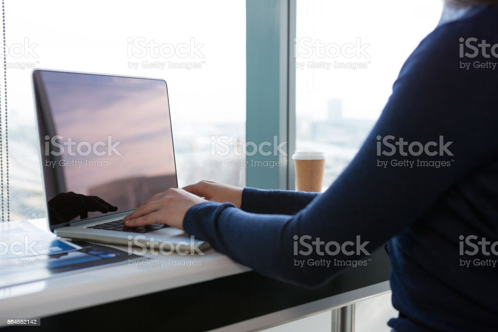 Mid section of female executive using laptop at desk stock photo