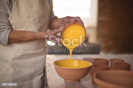 652188430 istock photo Mid section of female potter pouring watercolor in bowl 652188452