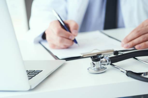 Mittelteil des männlichen Arztes schreiben Schreiben Rezept an den Patienten am Arbeitstisch. Allheilmittel und Lebensrettung, verschreibende Behandlung. – Foto