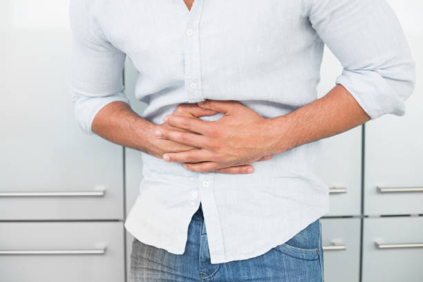 Mid section of man suffering from stomach pain stock photo