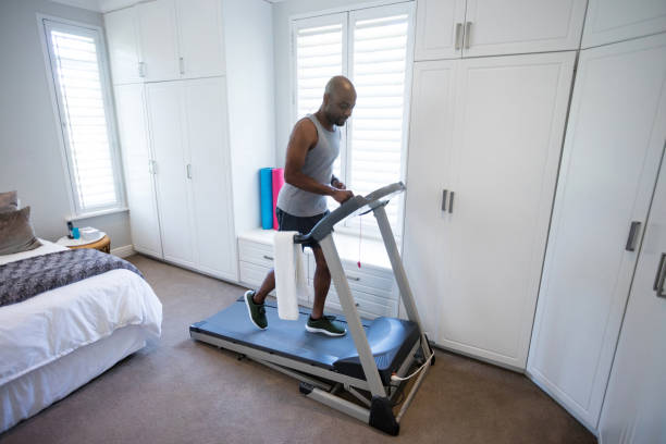 Mid section of man using smart watch while exercising on treadmill Mid section of man using smart watch while exercising on treadmill at home treadmill stock pictures, royalty-free photos & images