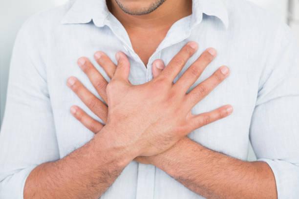 mid section of man with chest pain - mão no peito imagens e fotografias de stock