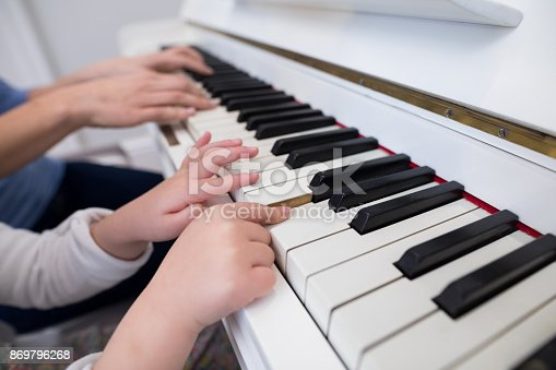 istock Mid section of mother and daughter playing piano 869796268