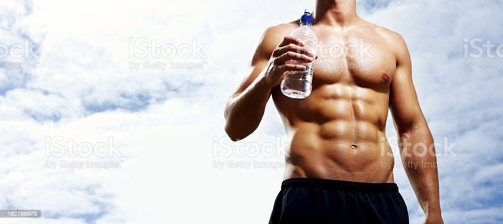 Mid section of muscular man with bottle aganist cloudy sky royalty-free stock photo
