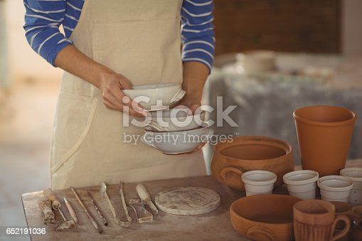 istock Mid section of potter holding bowl 652191036