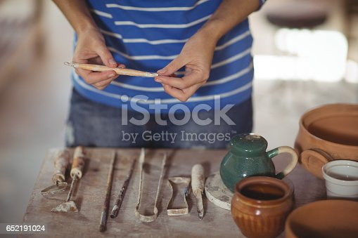 istock Mid section of potter holding work tool 652191024