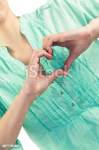 Mid section of woman with heart shape of fingers against white background