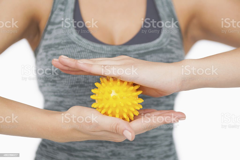 Mid section of young woman holding yellow massage ball stock photo