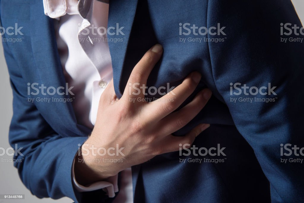 Mid section view of man having chest pain - heart attack - holding his heart in pain stock photo