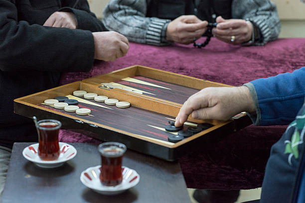 mid section view of two man playing backgammon - backgammon stock pictures, royalty-free photos & images