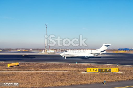istock Mid size modern vip private jet running on rairport runway ready to departure. Pilot asking air traffic control officer for take-off clearance. Luxury small corporate business aircraft trip 1203071350