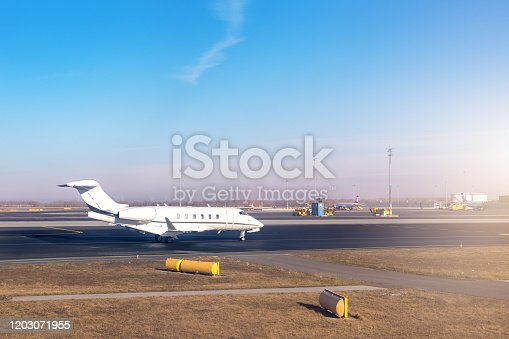 istock Mid size modern vip private jet running on rairport runway ready to departure. Pilot asking air traffic control officer for take-off clearance. Luxury small corporate business aircraft trip 1203071955