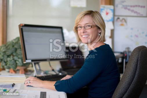 A woman in her mid thirties sits at a desk in front of a computer screen.Please see some similar pictures from my portfolio: