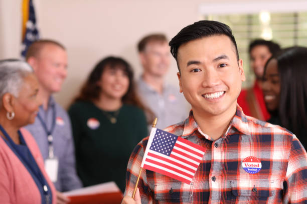 Mid-adult, Asian descent man votes in USA election. stock photo
