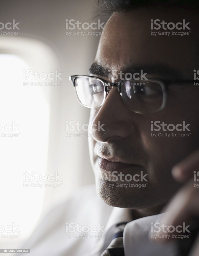 Milieu adulte Homme d'affaires, portant des lunettes, assis en avion, clo photo libre de droits