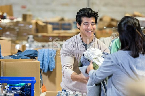 Young couple smile at each other as they volunteer for a charity event. The female passes a stack of folded clothes to her husband.