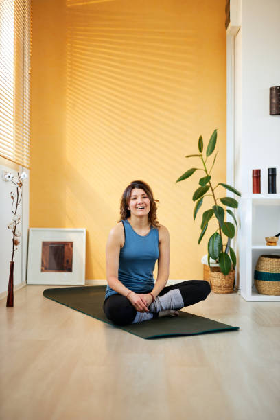 Mid-adult fit slim Caucasian brunette practicing morning yoga. Yoga teacher smiling in workout pause. stock photo