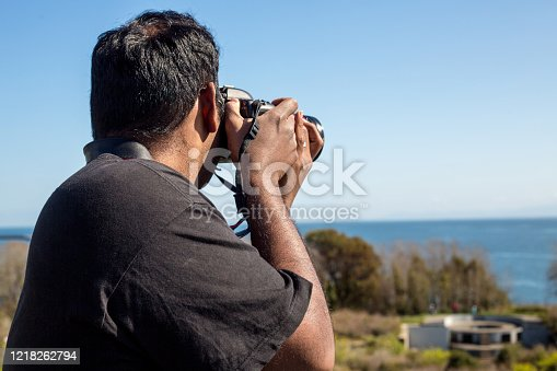 A mid-adult (31-year-old) man takes a picture in Victoria BC.