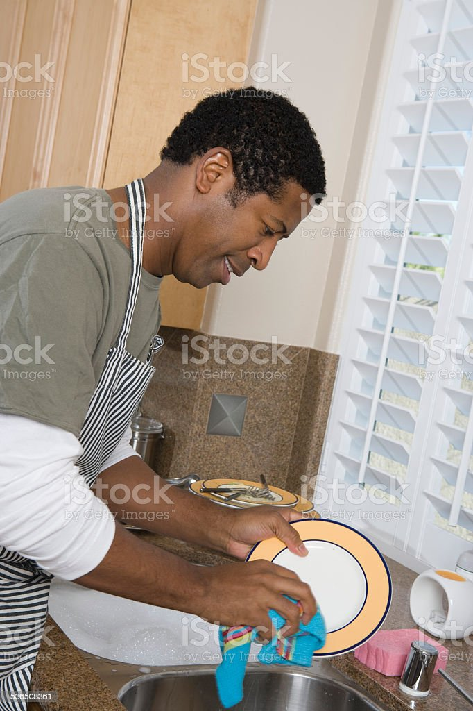 Mid-adult man washing dishes, smiling stock photo