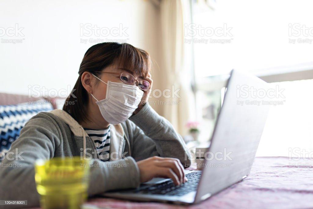 インフルエンザにかかり、自宅で働く中成人女性 - 1人のロイヤリティフリーストックフォト