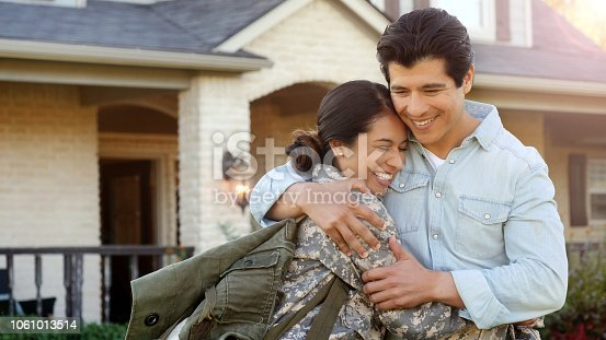 A smiling man pulls a smiling woman in uniform into a tight hug, while standing in front of home.