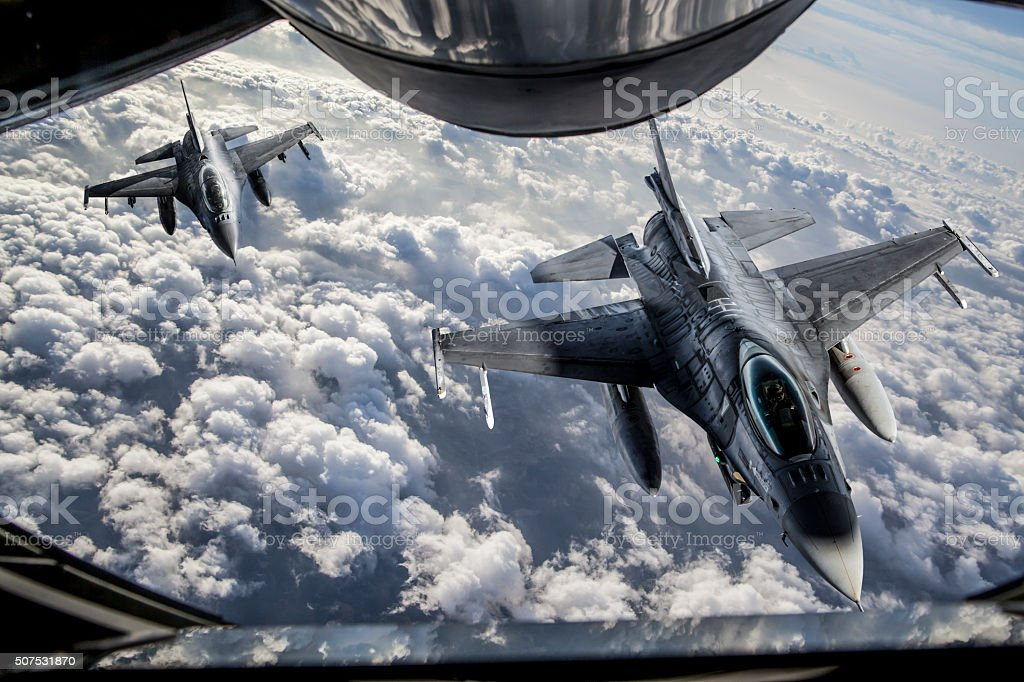 Mid-air Refueling Figher jets getting closer to KC-135 Stratotanker for mid-air refueling. Aerial View Stock Photo