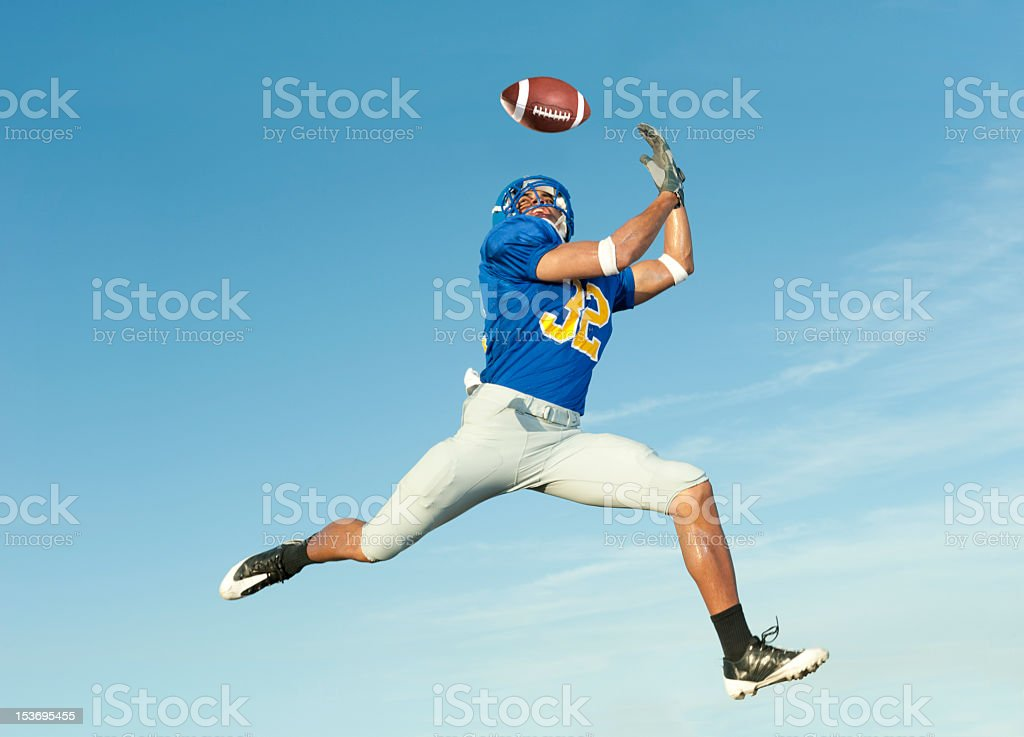 Mid-air shot of a player in blue catching a football stock photo