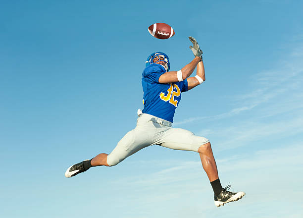 Mid-air shot of a player in blue catching a football Football player catches ball in midair. wide receiver athlete stock pictures, royalty-free photos & images
