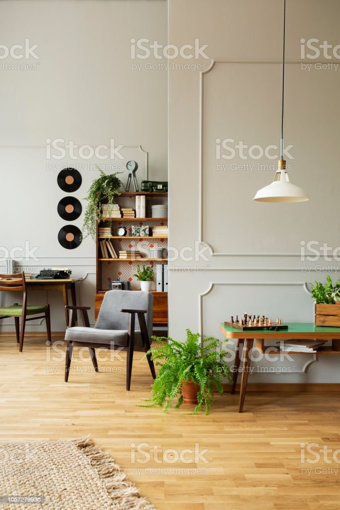 Mid-century modern armchair in a gray living room interior with wooden furniture, workspace and vintage decor. Real photo. stock photo