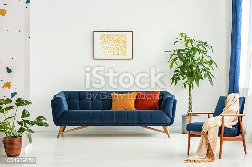 Mid-century modern chair with a blanket and a large sofa with colorful cushions in a spacious living room interior with green plants and white walls. Real photo.