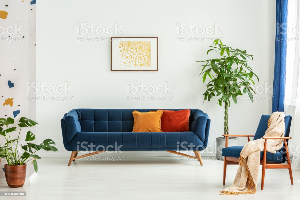 Mid-century modern chair with a blanket and a large sofa with colorful cushions in a spacious living room interior with green plants and white walls. Real photo. stock photo